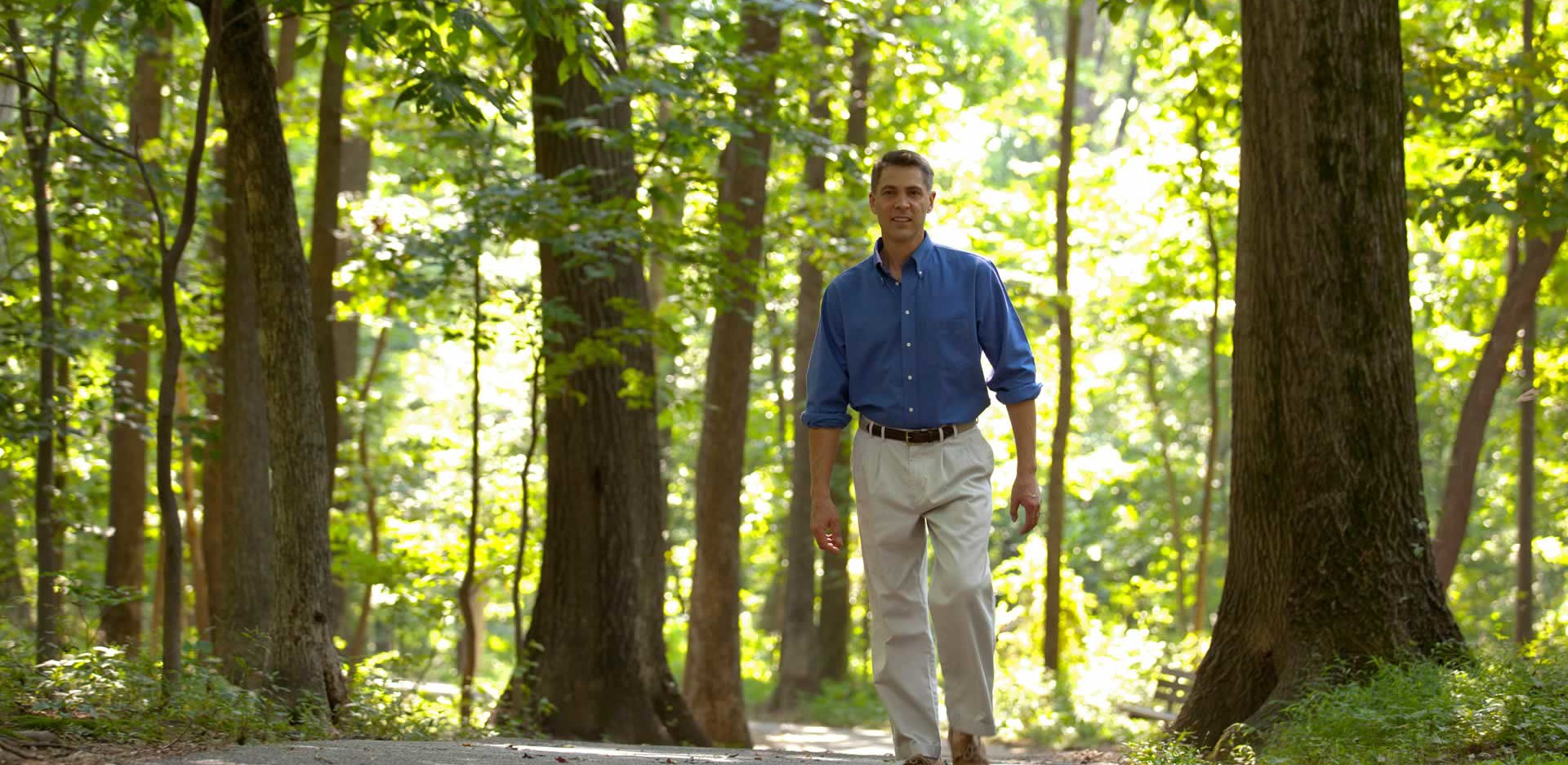 Roger Manno walking on path in the forest